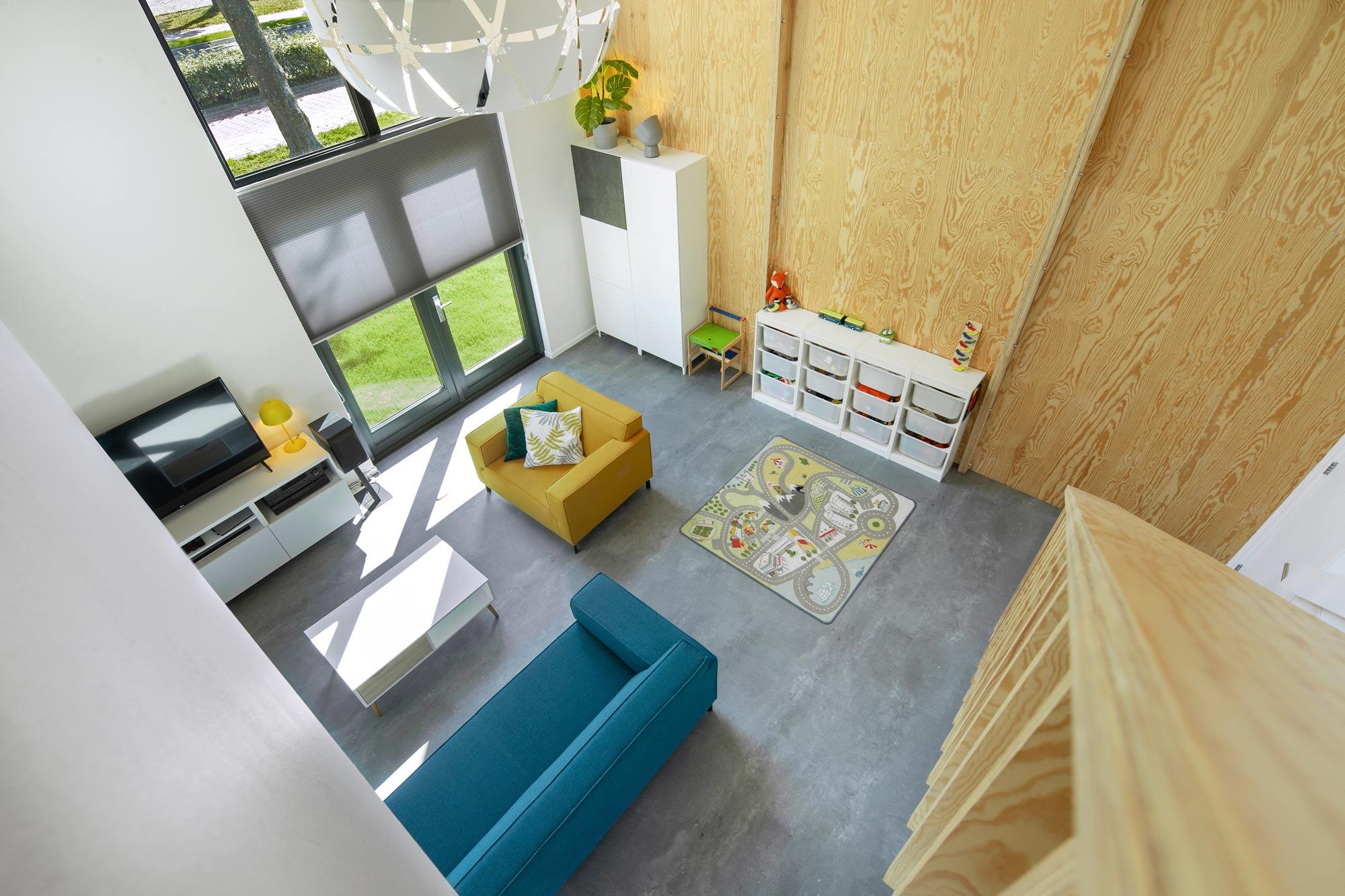 Zicht over woonkamer vanaf de vide