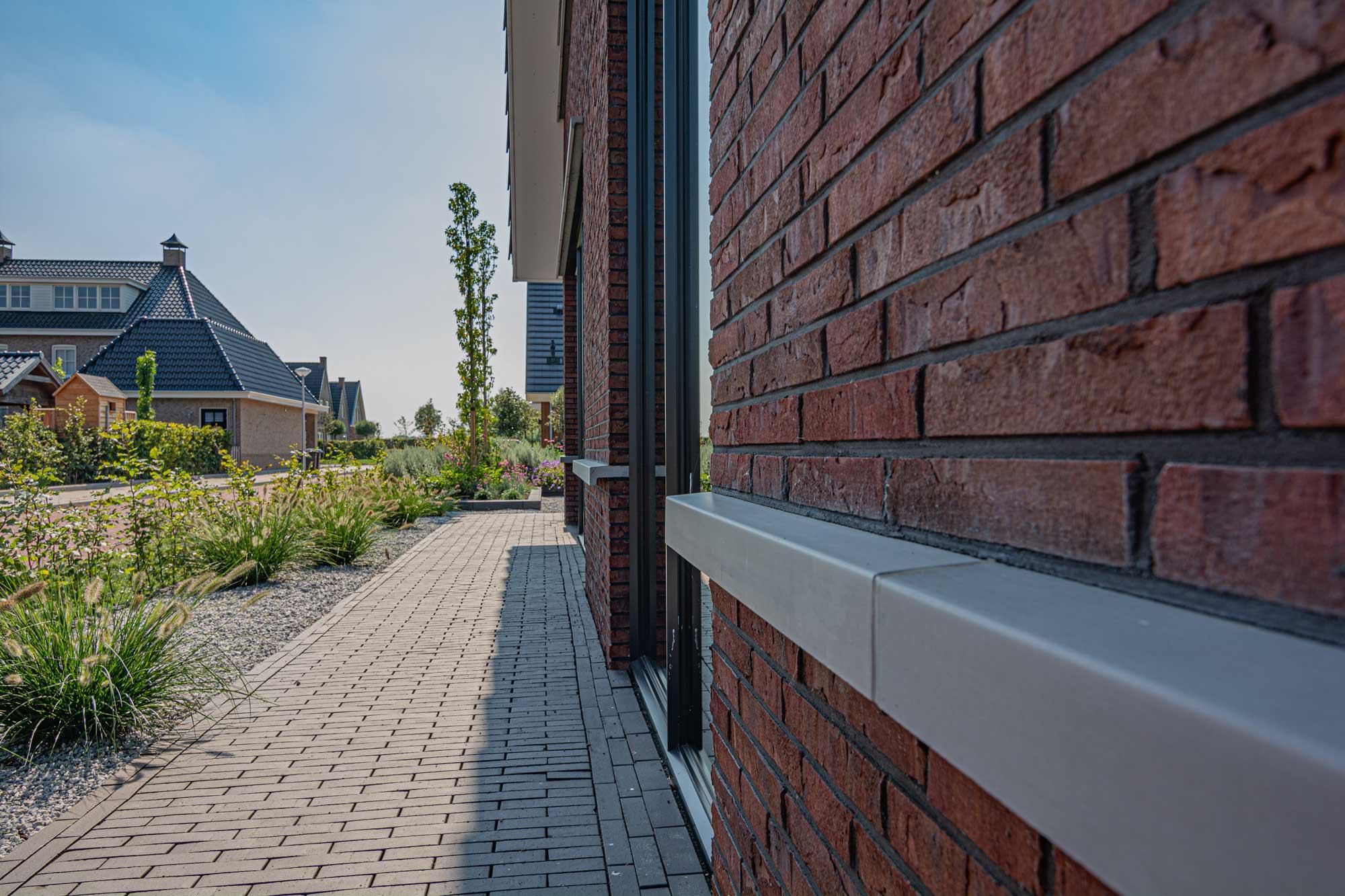 Bakstenen gevelafwerking met betonnen spekbanden